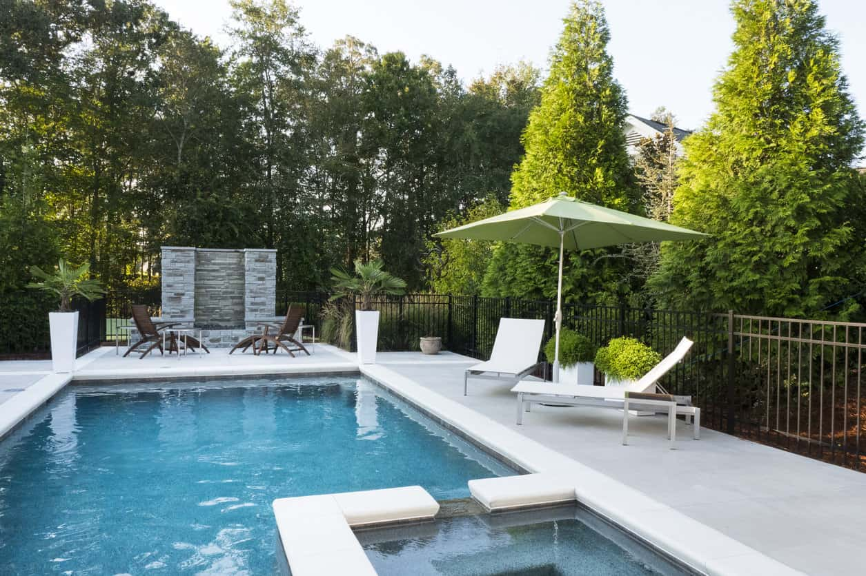 I like how the hot tub is embedded in the swimming pool. I also love the two-tone pool patio (white border with light grey patio). Also, notice the corner planters - that's a great idea any pool owner can incorporate easily.