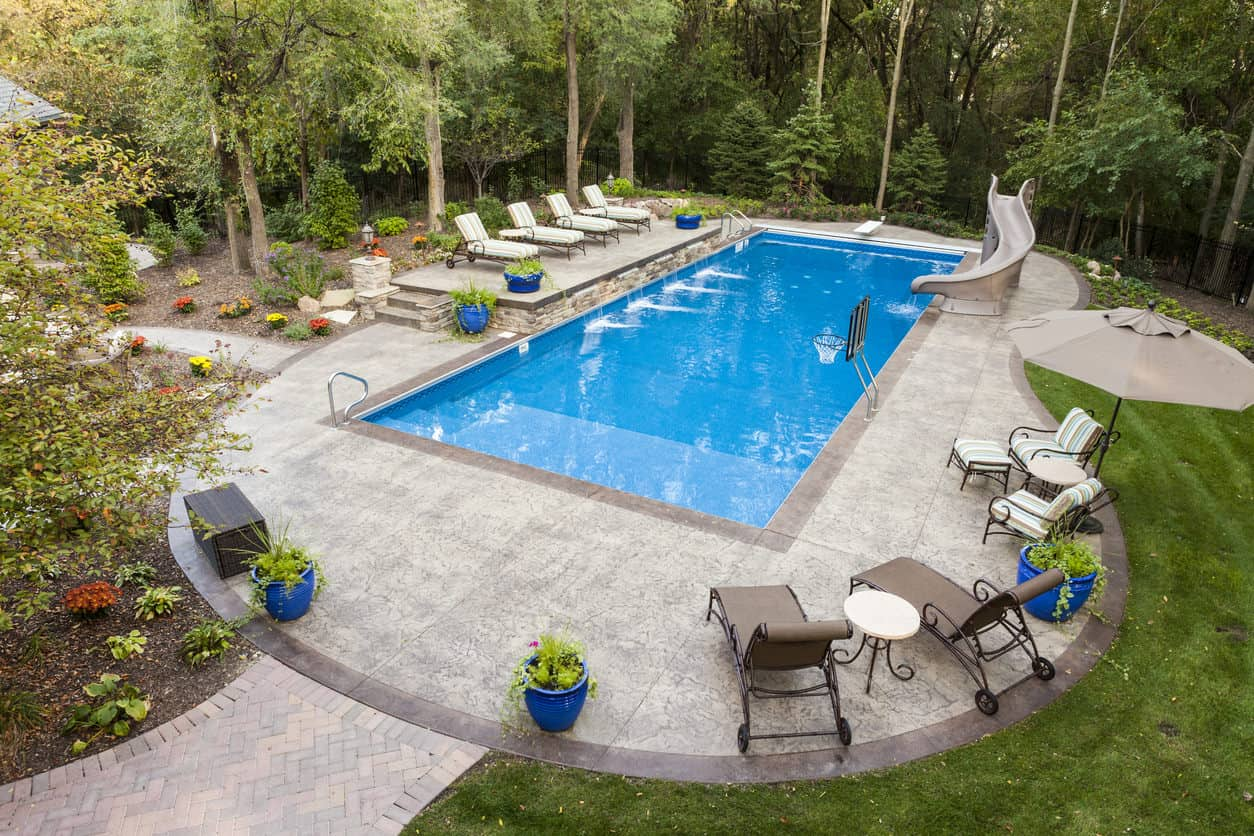 Now that's just one big kids' area in the backyard - large rectangle pool with a slide, basketball hoop surrounded by wrap-around patio which is in turn surrounded by gardens, grass and trees.