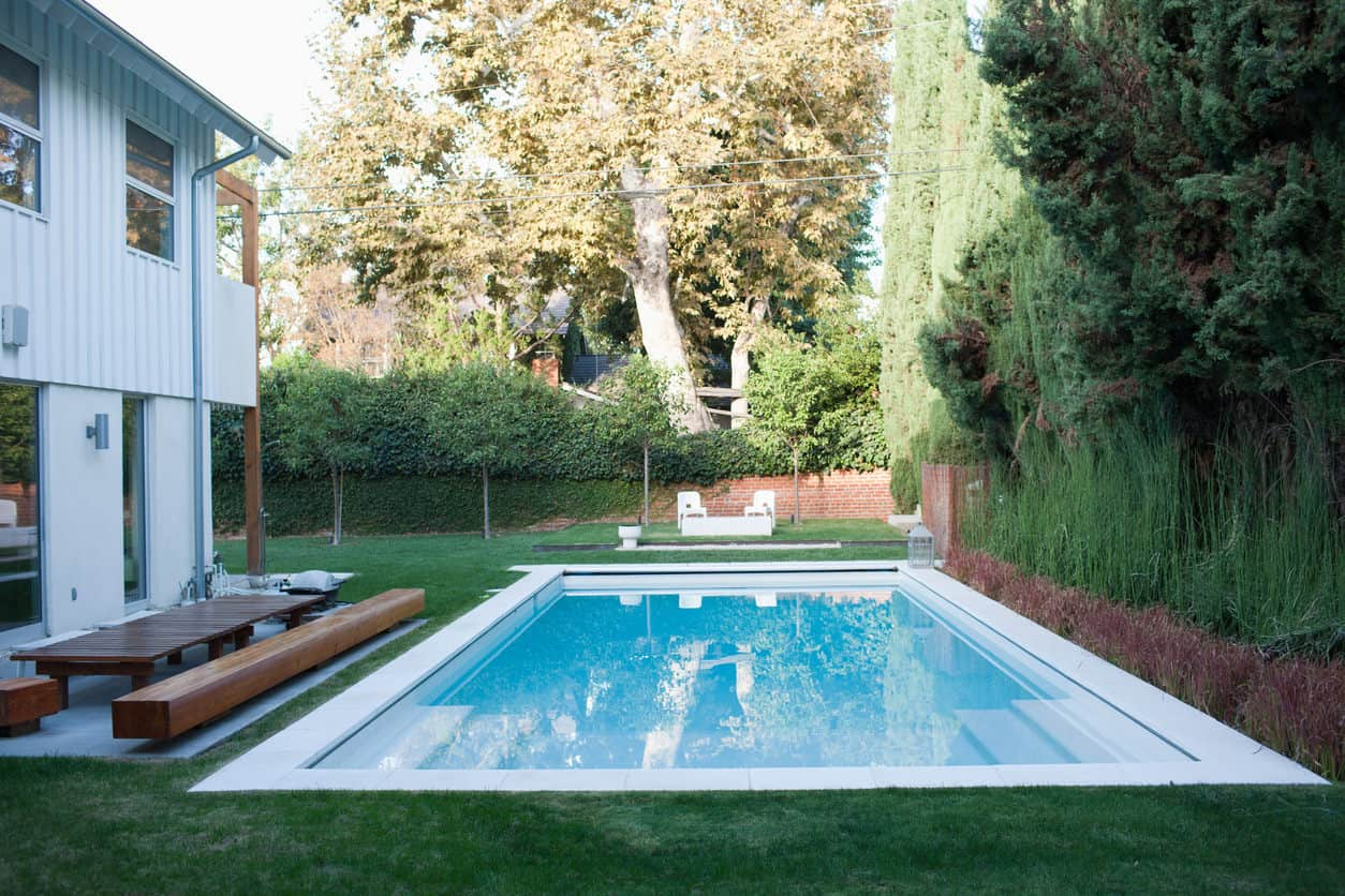 Here's a small grassed-in backyard with a pool that has no patio around it. Interesting. I definitely prefer pools with a deck or patio, but this is an example of one without.