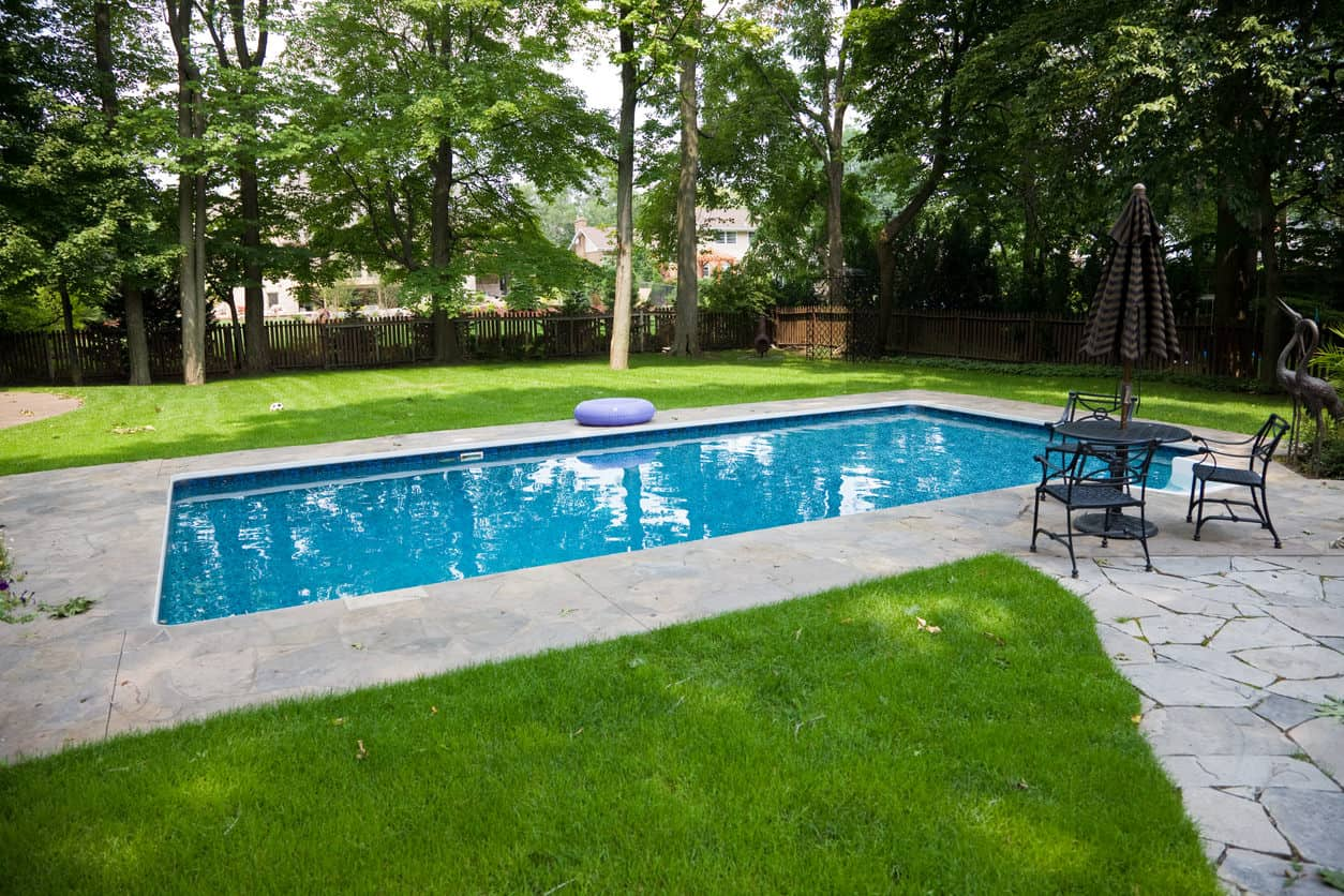 Here's an island pool. By island pool I refer to a pool patio not fully attached to the patio off the house. The pool and patio is in the middle of the yard. This is a hybrid version since there's a flagstone walkway leading from the house to the patio, but the effect is the same.
