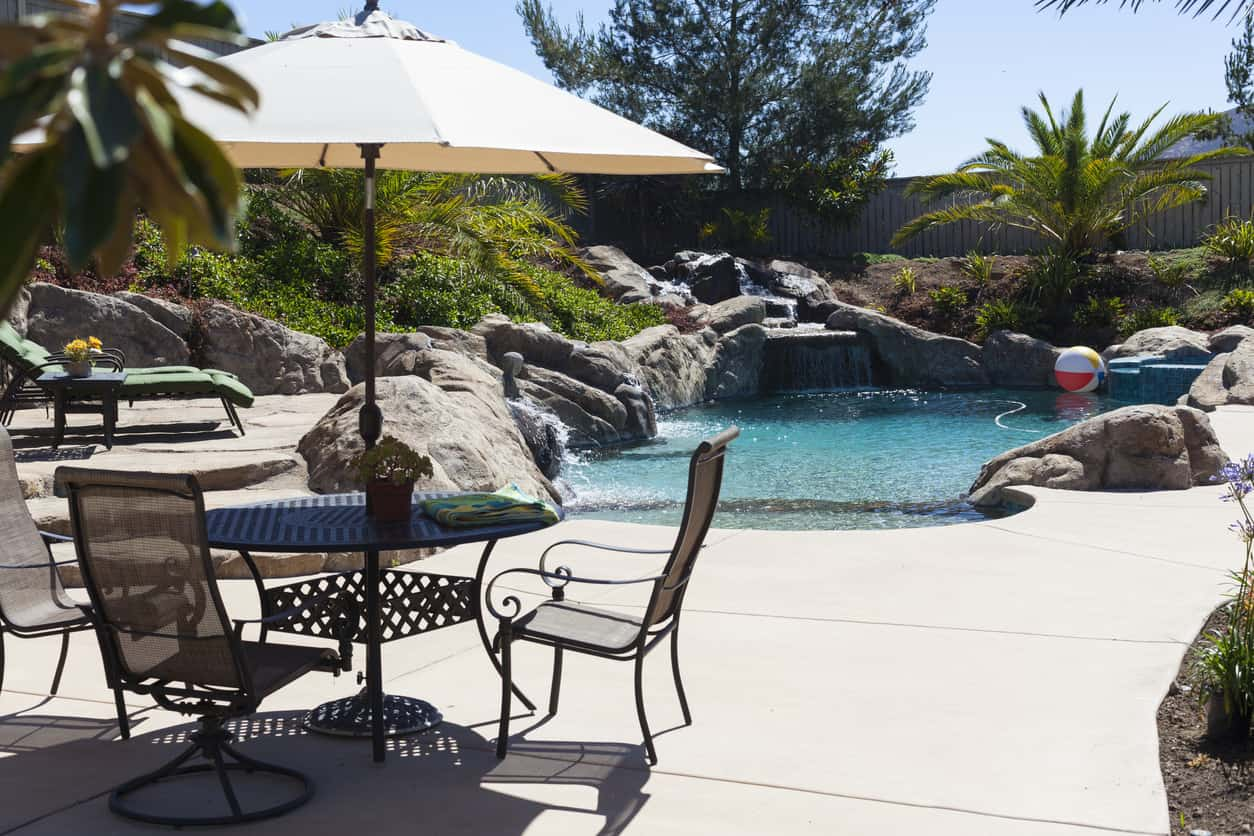 This small backyard pool is all about the landscaping. Check out the rock work and waterfall flowing into the pool. It looks just like a river pool. Notice the elevated lounging area overlooking the pool as well. This is a stunning backyard.