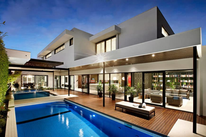 Modern home featuring a gray exterior and a gorgeous outdoor area with a swimming pool.