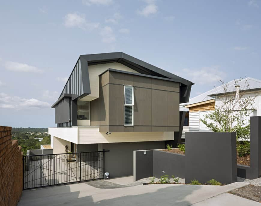A modern home featuring a gray exterior, a driveway with a gate and a nice garage.