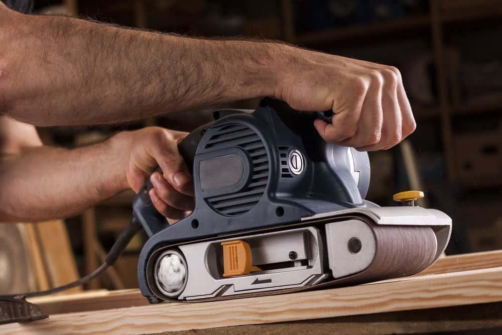 Man's hands holding a belt sander on a slab of wood in a workshop.