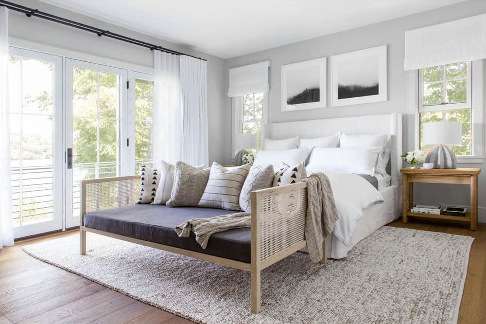 White bedroom with lots of windows and medium hardwood flooring with area rug.