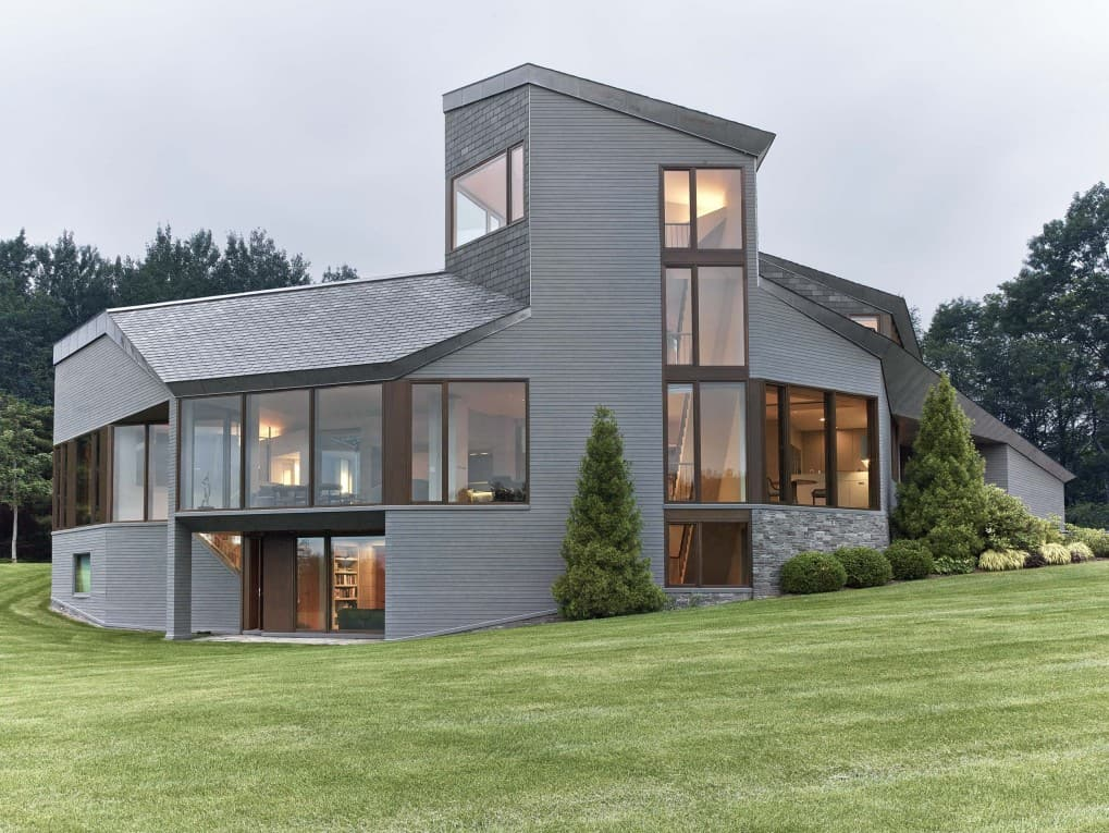 This mountain house has a modish look and features a gray exterior, surrounded by a sprawling and beautiful lawn area.