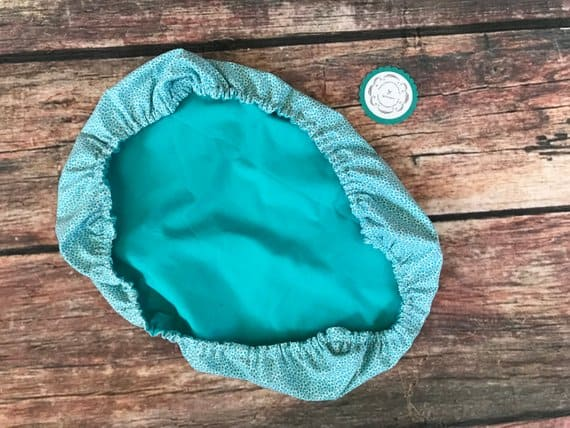 Green fabric bowl cover on wooden background.