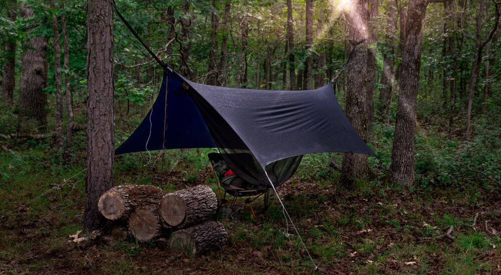 A hammock tent is pitched in the woods.