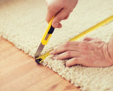A man is using a utility knife to cut a portion of the carpet.