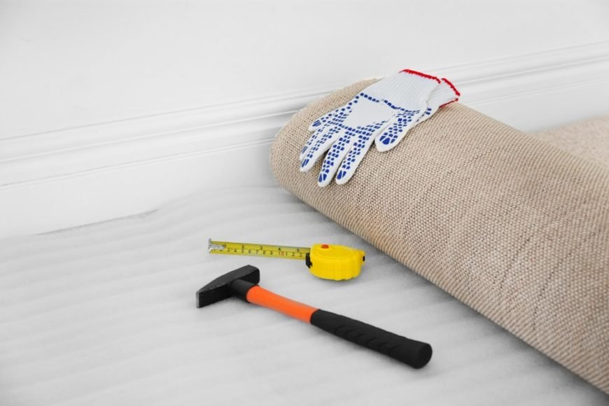 A set of carpet tools such as hammer, measuring tape, and gloves.