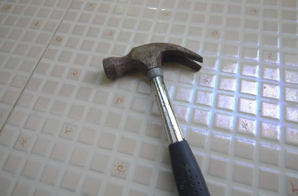 A claw hammer resting on floor tiles.