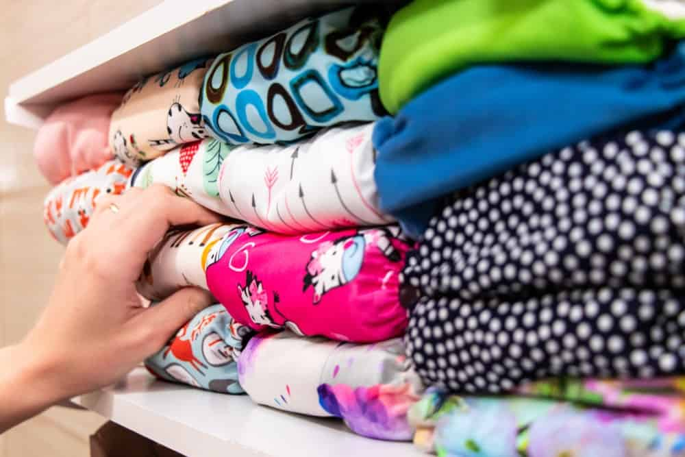 Hand reaching out to one of the colorful cloth diapers stacked on an open shelving.