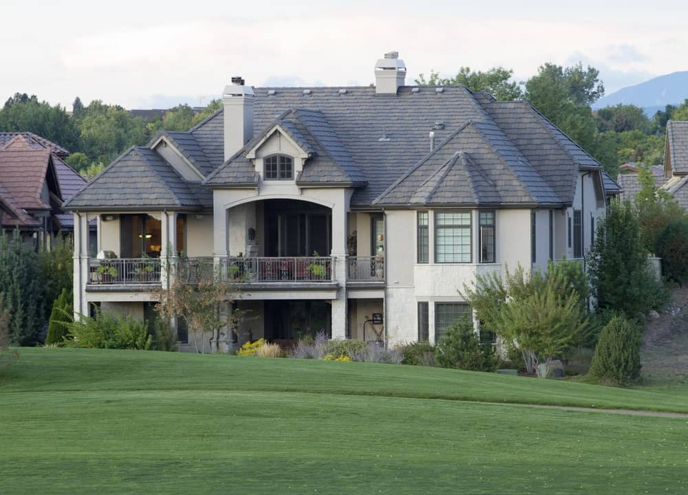 Colorado mansion with gray stucco exterior facing a golf course.