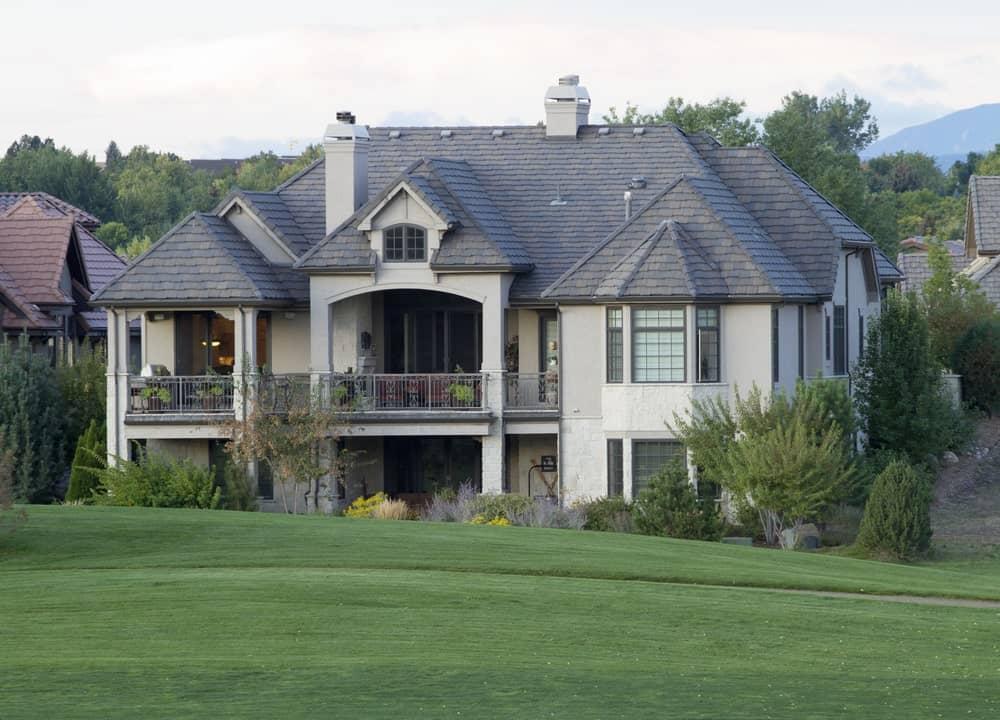 Colorado mansion with gray stucco exterior facing a golf course.