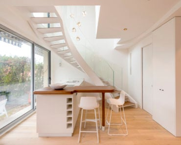 Small modern white kitchen under curved staircase