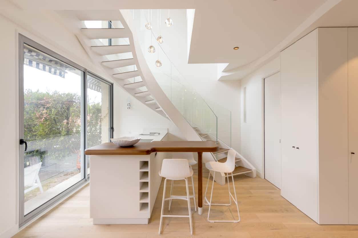 Cool small white and natural wood small kitchen with wine storage, breakfast bar and winding staircase dropping overhead. This is a super smart design for a two-level apartment.