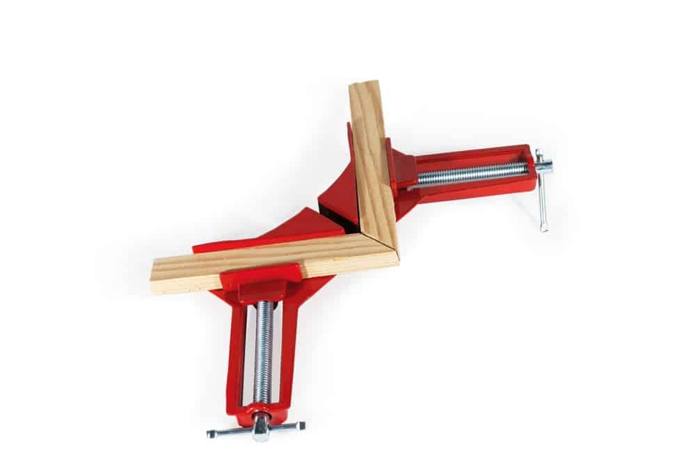 Corner clamps used to hold two pieces of wood in place on white background.