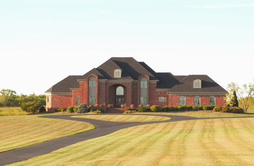 Countryside mansion with brick-color facade, spacious front area, and asphalt driveway.