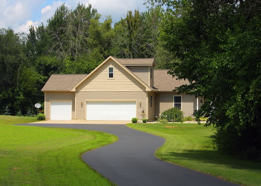 Countryside with asphalt driveway and one-door garage.