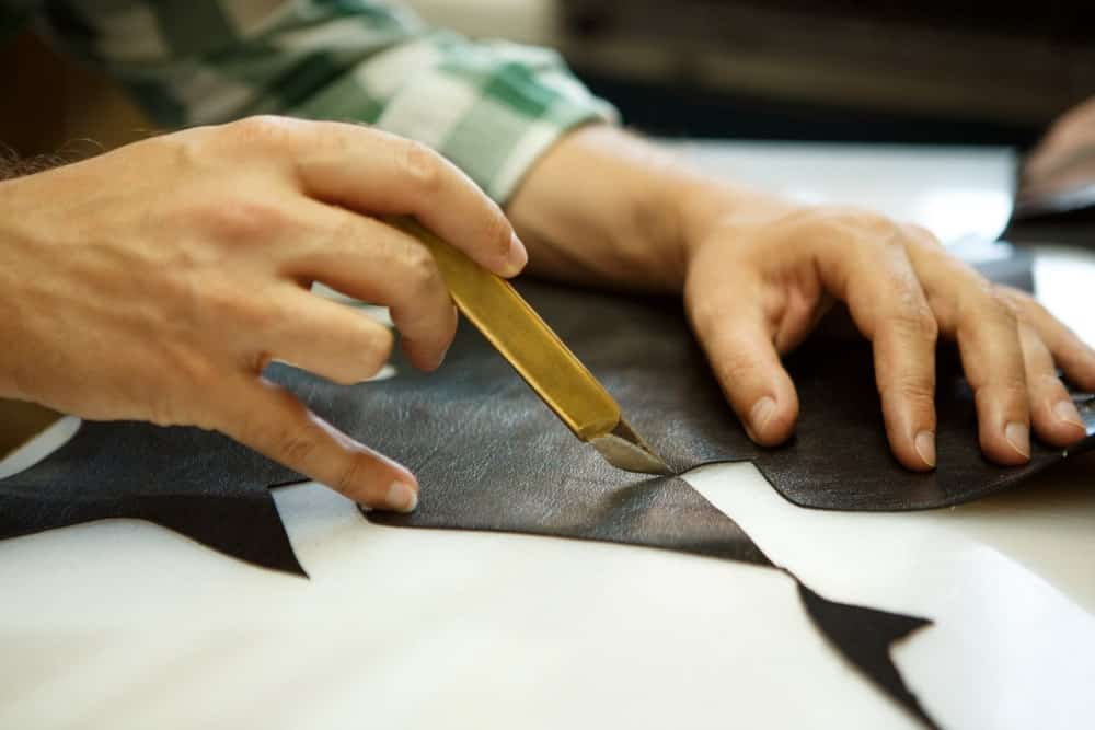 Cutting leather with a craft knife.