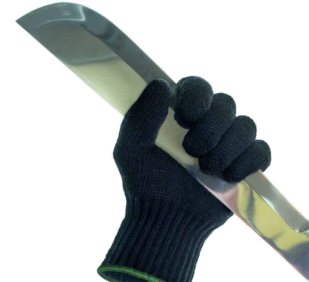 Hand-resistant glove holding a large knife.