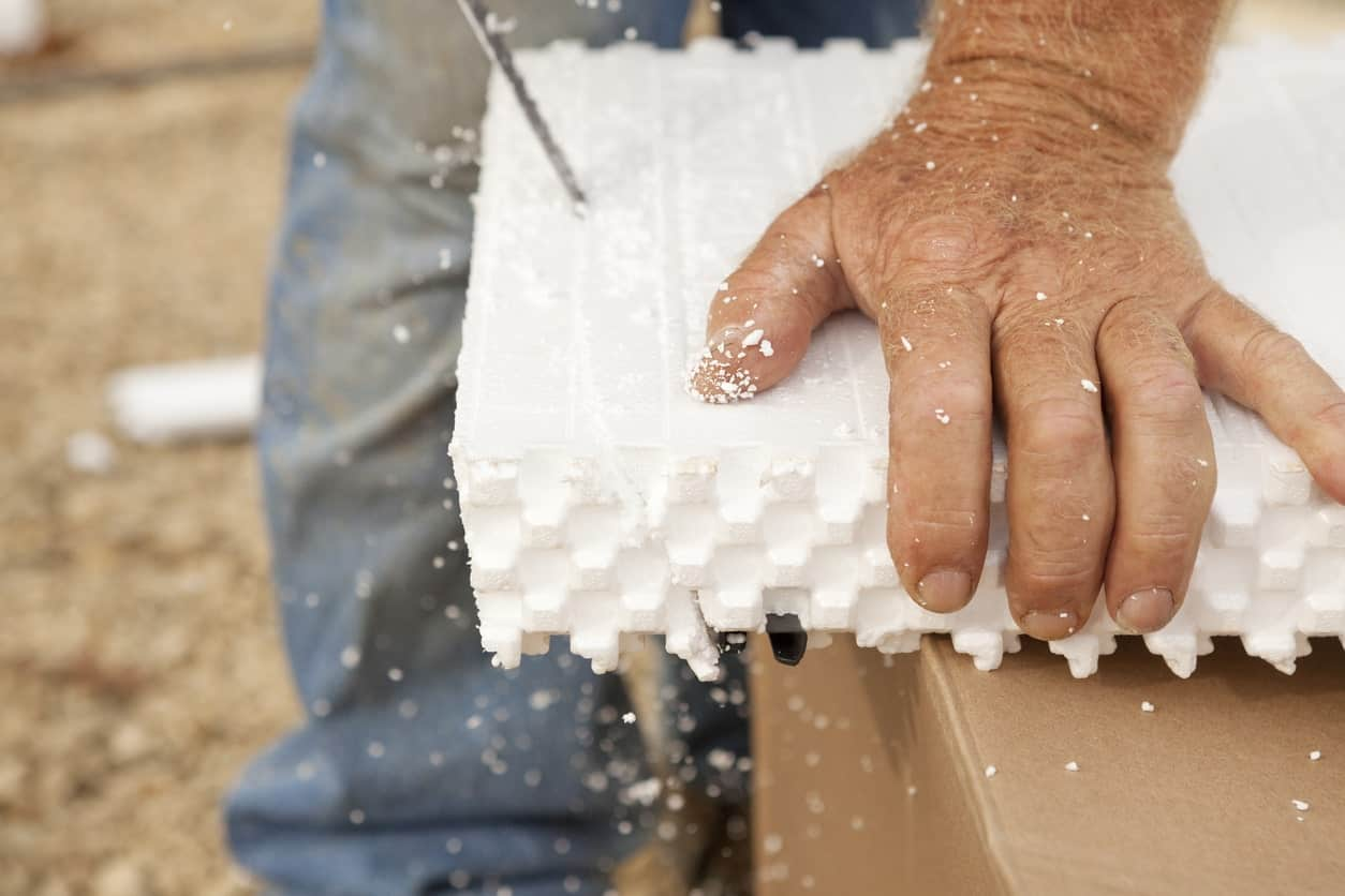 Hand holding down a thick styrofoam while it is being cut.