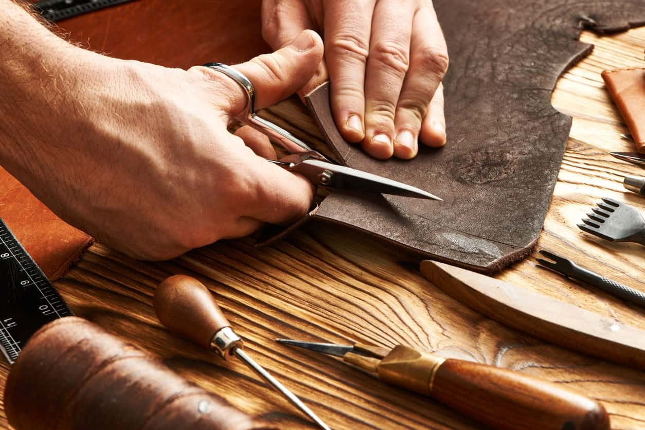 Cutting leather with leather craft tools on the desk.