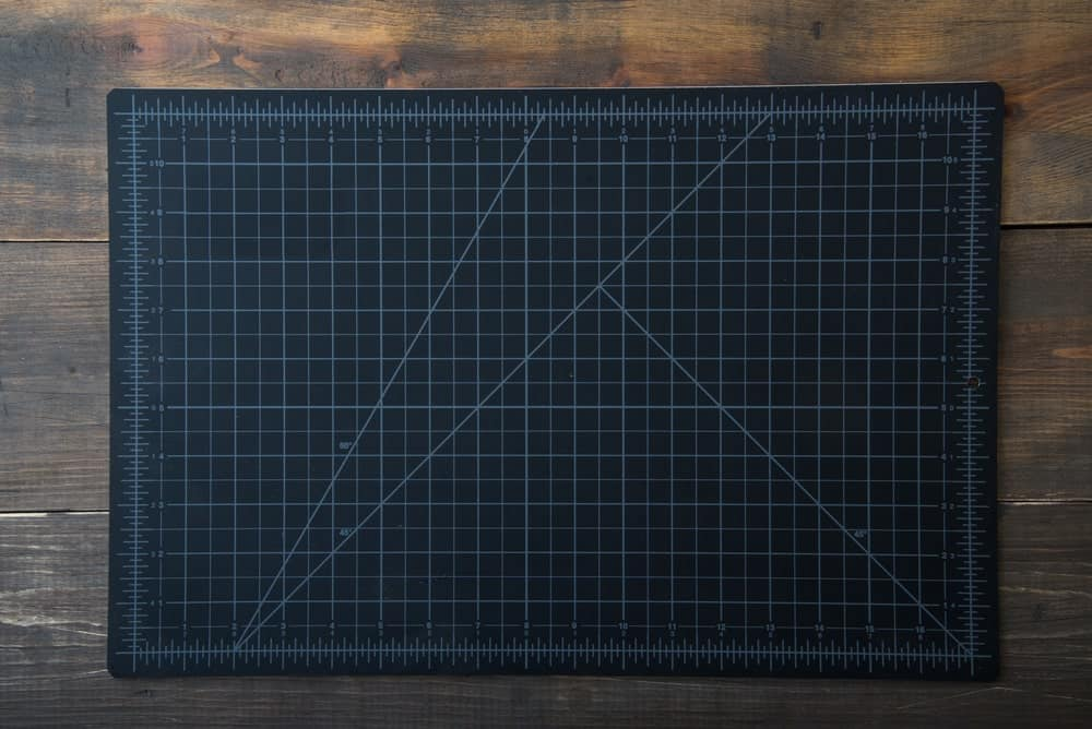 Cutting mat on wooden background.