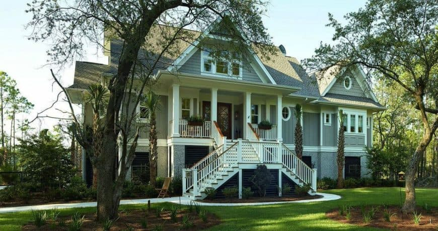 A custom gray home featuring a beautiful and well-maintained lawn area.