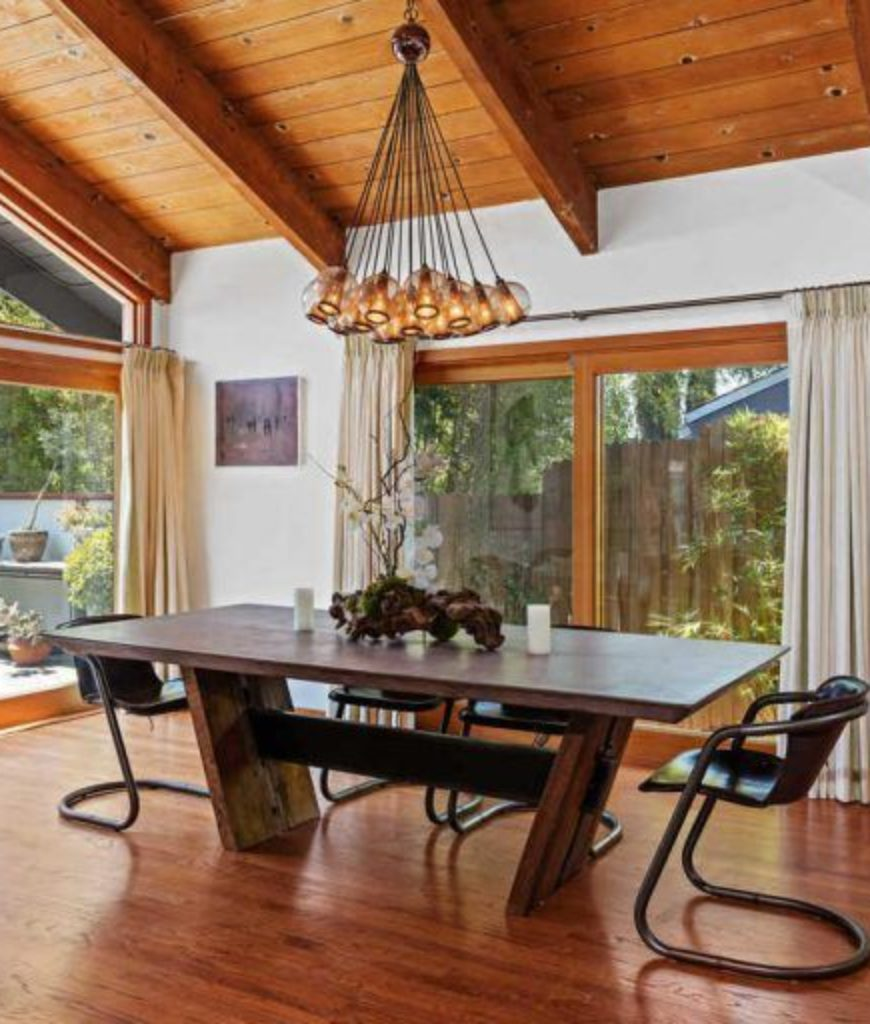 The dining room looks stylish with its table and chairs set lighted by a stunning pendant lighting.