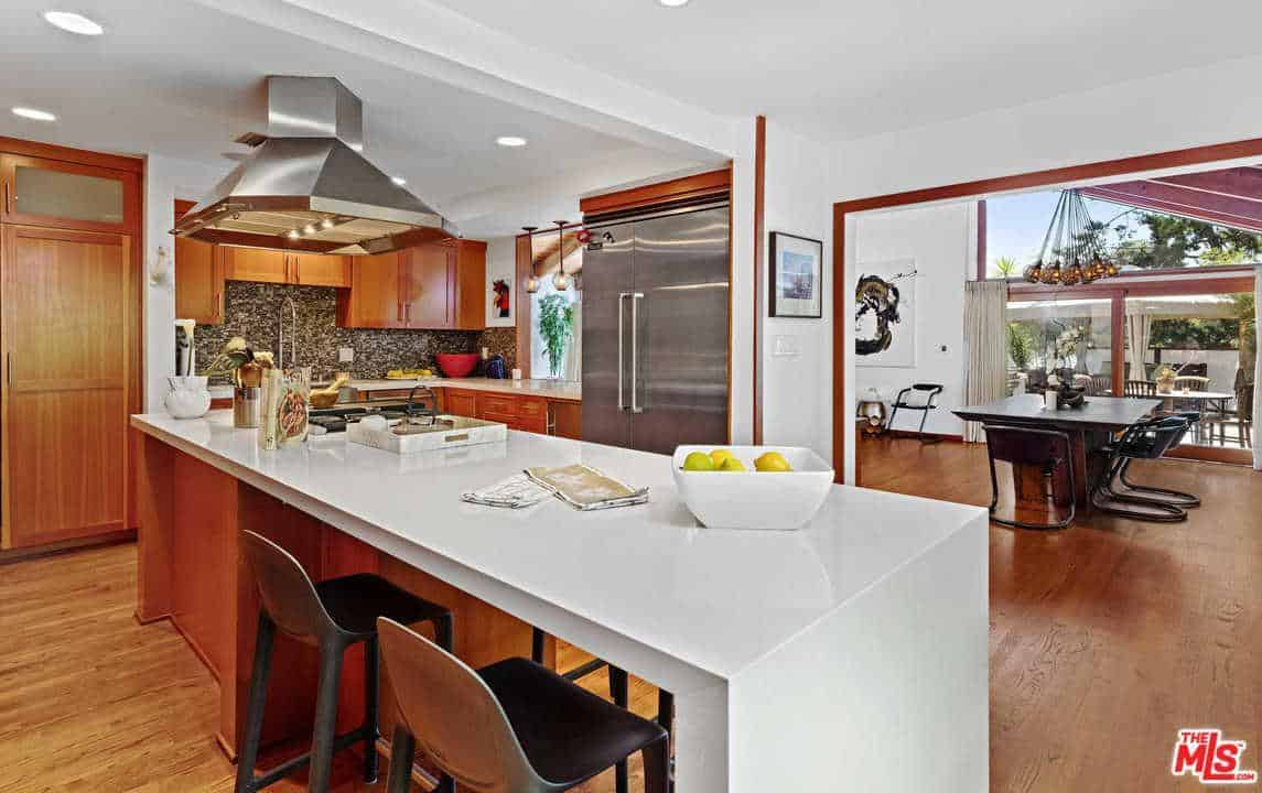 The kitchen has a breakfast bar with a smooth white countertop.