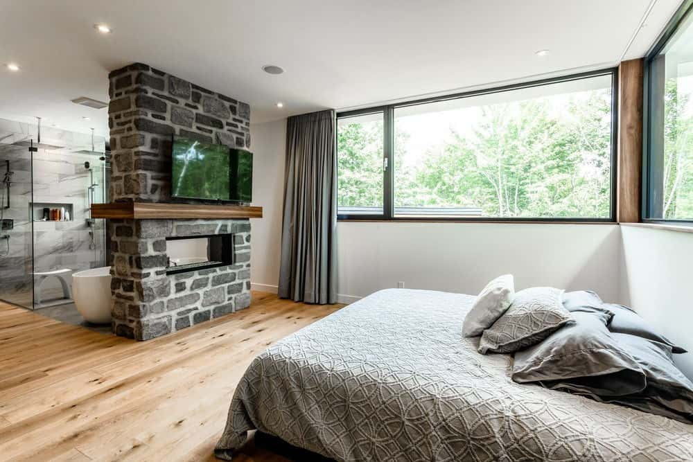 This primary bedroom showcases a gorgeous brick wall that serves as a divider to the open bathroom. It is surrounded by glass windows covered with gray curtains.
