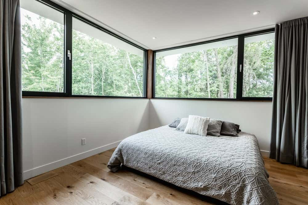 Close up view of the bedroom's large bed and glass windows. Photo credit: Dominic Boudreau
