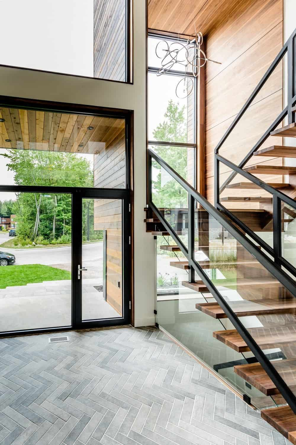 The entry features a modish staircase and stylish doorway. Photo credit: Dominic Boudreau