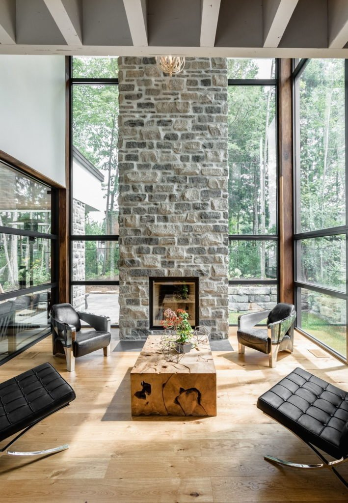 High ceiling living room boasts light wood plank flooring and full height glazing lined with a stone brick fireplace. It includes black modern seats surrounding a stump coffee table topped with geometric decors.