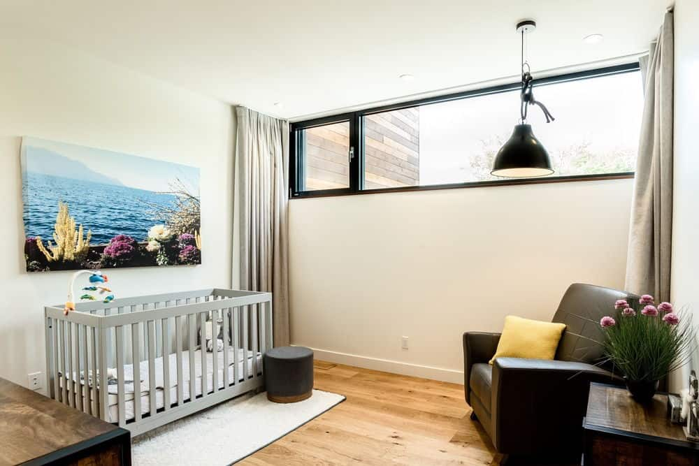 Another nursery room featuring a gray baby crib and a club chair along with a wall decor. Photo credit: Dominic Boudreau