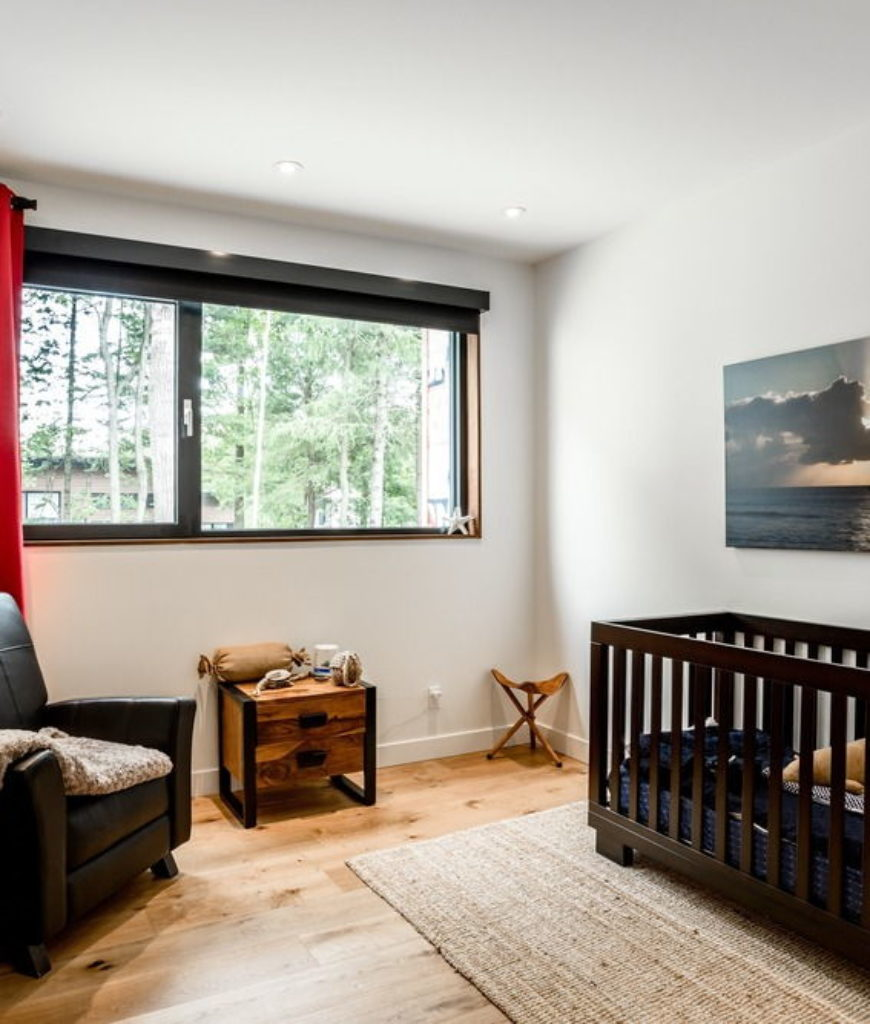 There's a nursery room showcasing a stylish baby crib and a club chair along with a stylish wall decor. Photo credit: Dominic Boudreau