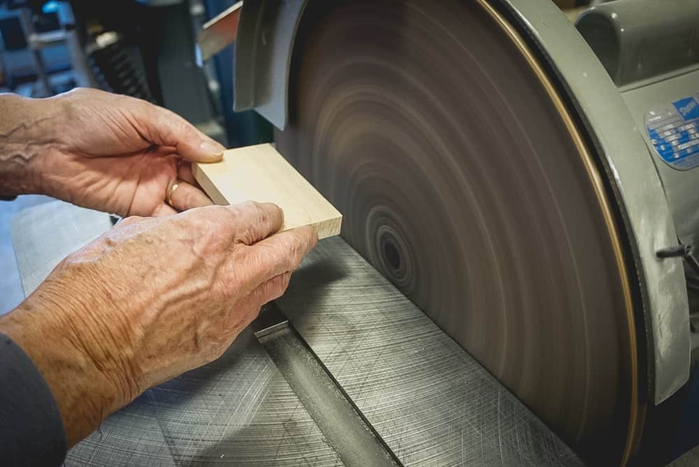 Old hands holding a small block of wood in front of a rotating disc sander.