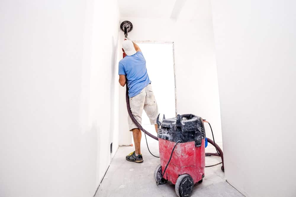 Back view of a man polishing the newly painted white walls with a drywall sander.