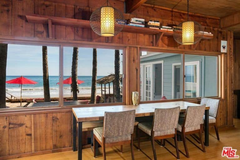 The dining area surrounded by hardwood materials and lighted by pendant lights overlooks the lively beach front.