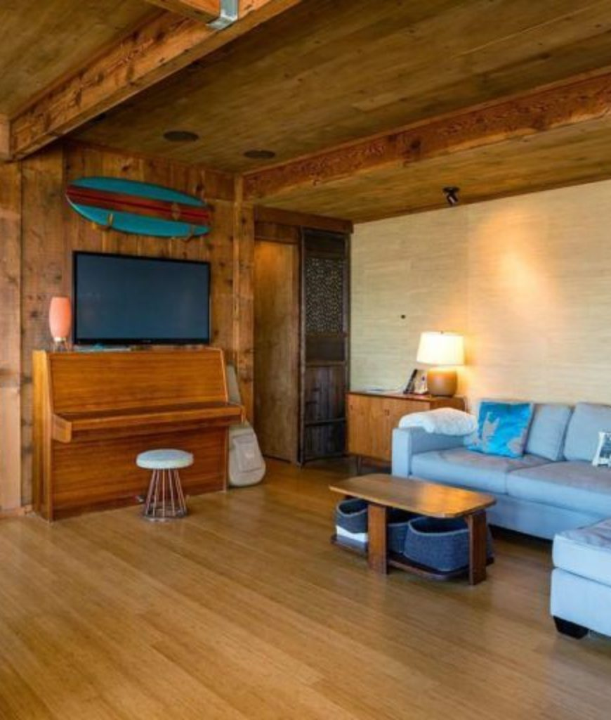 The living space features hardwood floors, walls and ceiling along with cozy seats and a TV on wall.