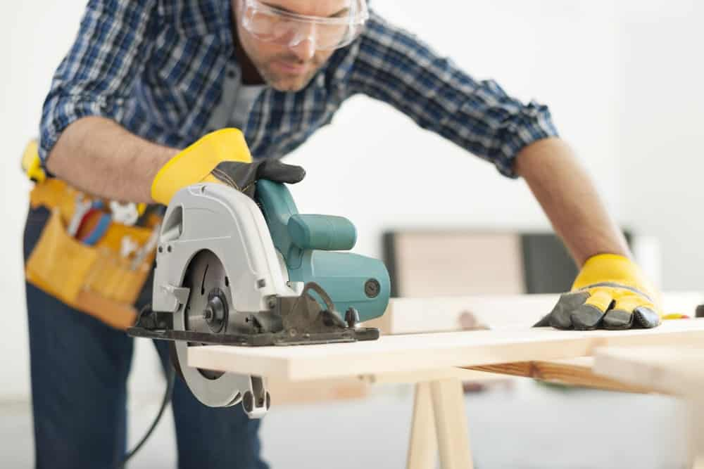 A man wearing safety goggles, toolbelt, and rubber gloves use an electric table saw to cut a piece of wood.