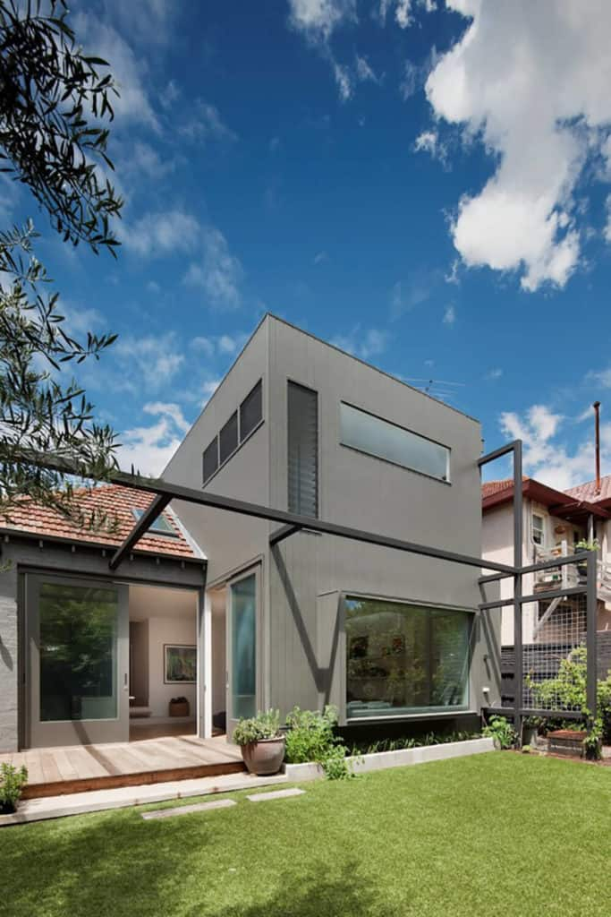This modern house has a gray exterior and has a well-maintained lawn area.
