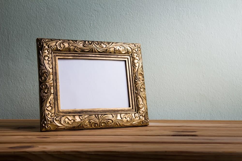 Empty rectangular picture frame on wooden desk.
