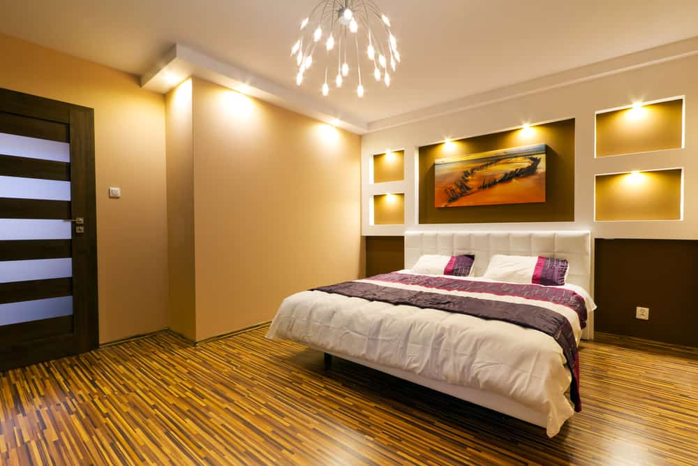 Photo example of a primary bedroom with modern wall lighting.