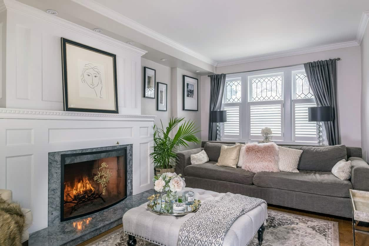 Traditional formal living room with white surface fireplace (with beautiful molding) surrounded by gray traditional living room furniture including an elegant white tufted square ottoman serving as coffee table.