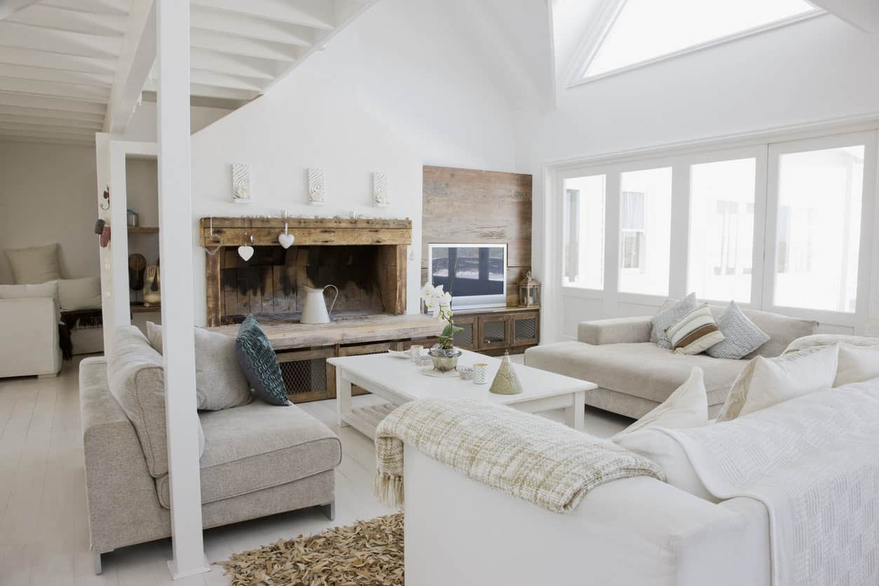 Here's a light rustic living room with towering white ceiling and distressed beamed fireplace mantel. The light beige sofas tie in the distressed wood with the otherwise all white space.