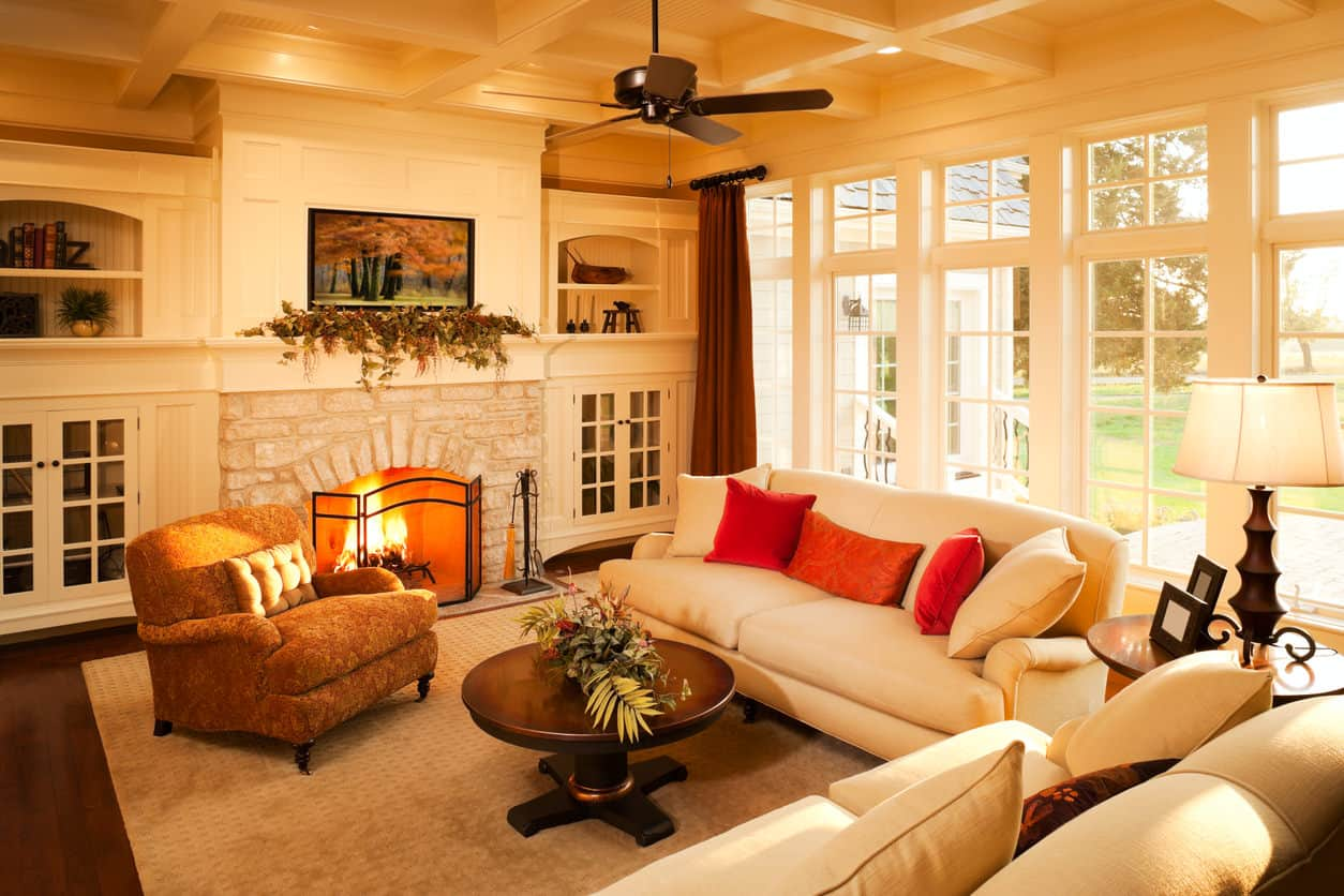 Sun-filled traditional living room with incredible white built-in cabinets flanking and surrounding the brick fireplace. Casual white leather sofas make up the furniture plus a retro orange armchair matched with orange throw pillows on the sofas. It's hard not to like this living room with all the custom woodwork including the stunning coffered ceiling.