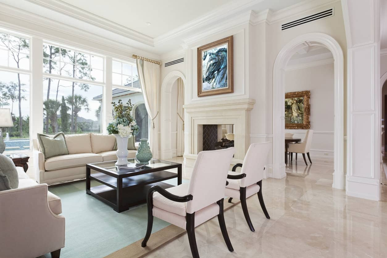Elegant white formal living room with two sofas and two accent chairs. I love the arched doorways flanking the fireplace and of course the huge floor-to-ceiling window. The tall ceilings with crown molding is also a fabulous feature. This is the epitomy of a formal living room.