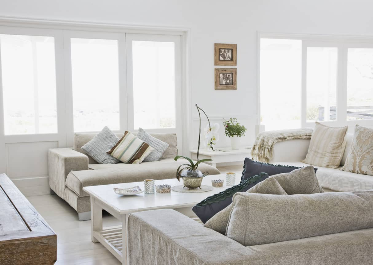 Casual beach style living room with light beige and white ultra deep sofas circling around a large white coffee table. I just want to sink into those deep sofas.